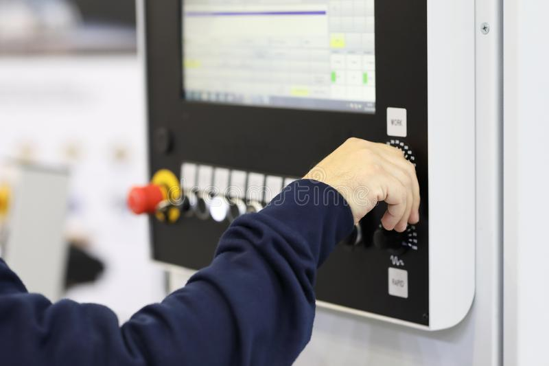操作员控制CNC机器的工作 免版税库存图片