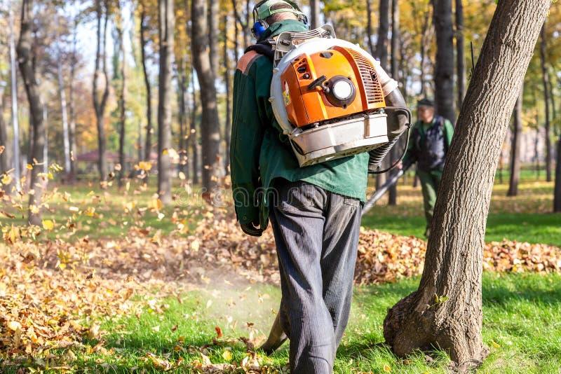 操作耐用吹叶机的工作者在城市公园 在秋天去除落叶 打旋的叶子  叶子 免版税库存图片
