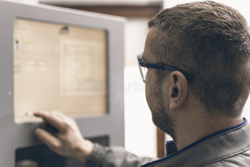操作CNC机器的工作者在工厂 塑料窗口和门 免版税库存照片