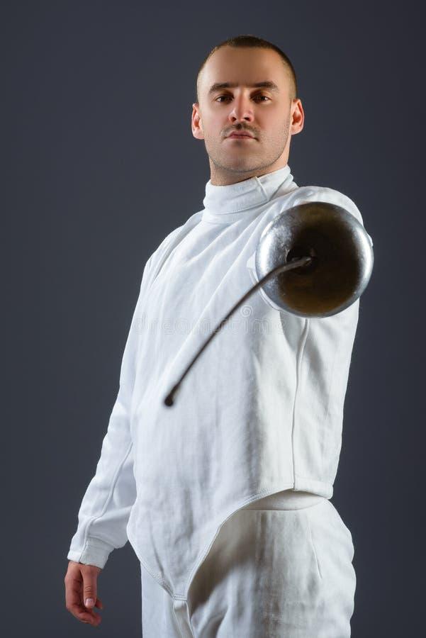 操刀摆在与一把剑或锐剑的运动员在灰色背景 免版税图库摄影