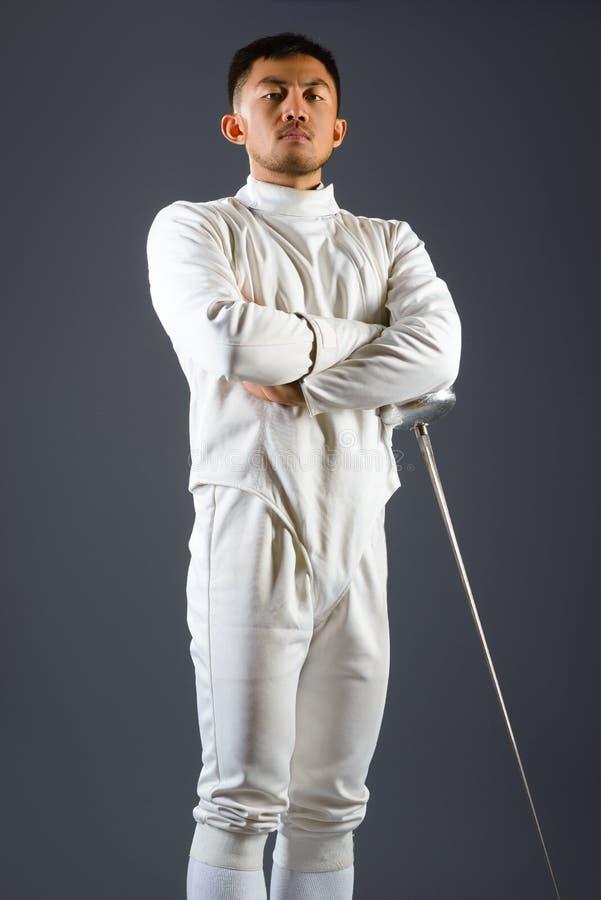 操刀摆在与一把剑或锐剑的运动员在灰色背景 免版税库存图片