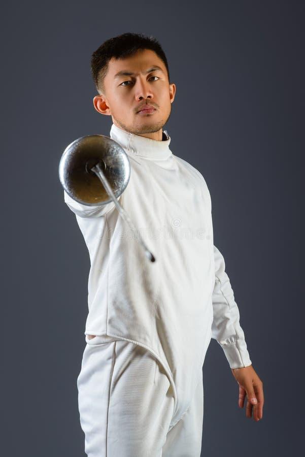 操刀摆在与一把剑或锐剑的运动员在灰色背景 库存照片