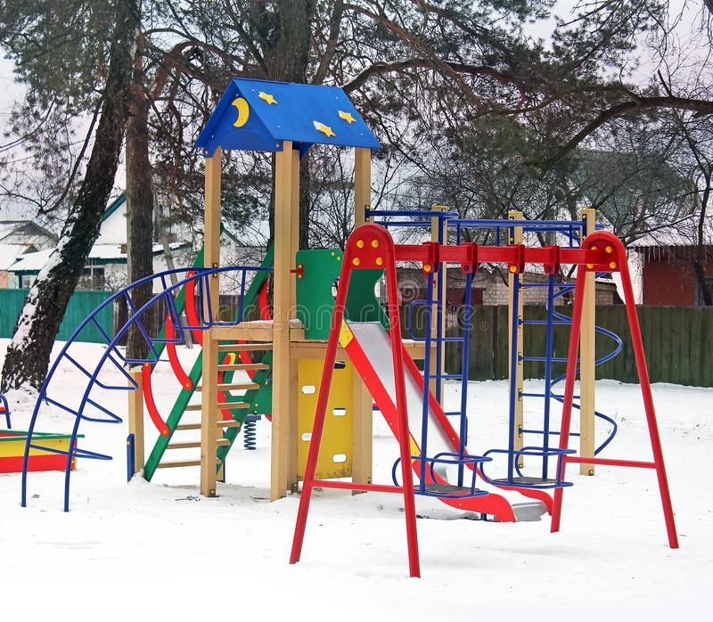 操场在冬天 雪的儿童的游乐场 儿童` s摇摆 免版税库存图片