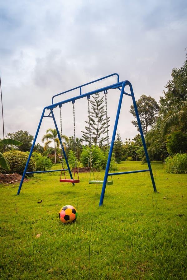 操场在绿草的设备在孩子的后院与足球目标网和橄榄球调遣背景 免版税库存图片