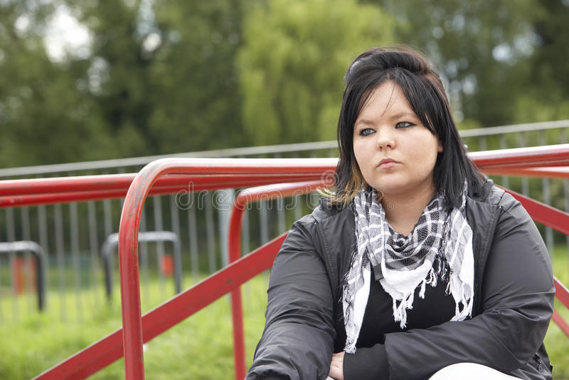 操场坐的妇女年轻人 免版税库存图片