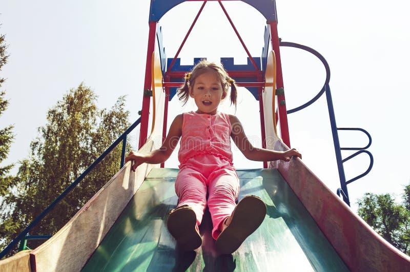 操场或玩耍区域是为了孩子设计的区域能使用,户内或户外, A小女孩滚动下来一张老金属幻灯片 免版税库存图片