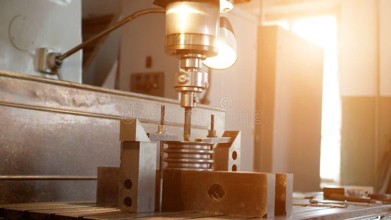 操练与一台钻床的一个孔在金属制件滑轮,特写镜头,产业,制造的杜松子酒 免版税图库摄影