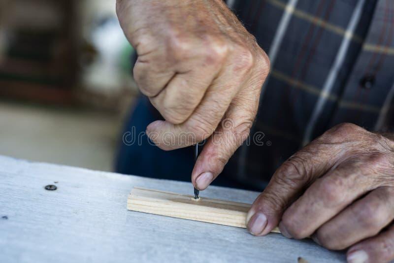 操练与手钻的老人木小条 图库摄影