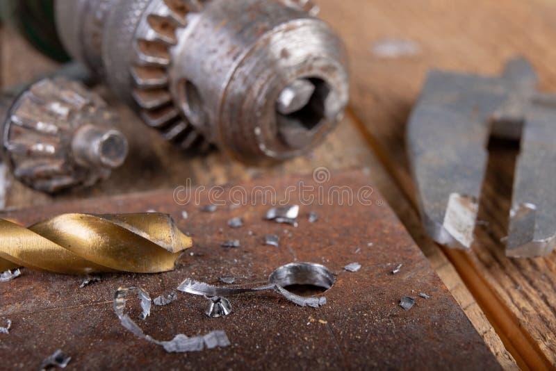 操练与金属钻子 小锁匠工作在家庭车间 免版税库存图片