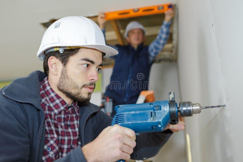 操练混凝土墙建造场所的工作者 免版税库存照片
