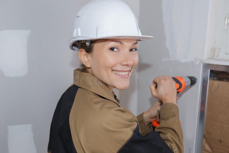 操练混凝土墙的安全帽的女性建筑工人 库存照片