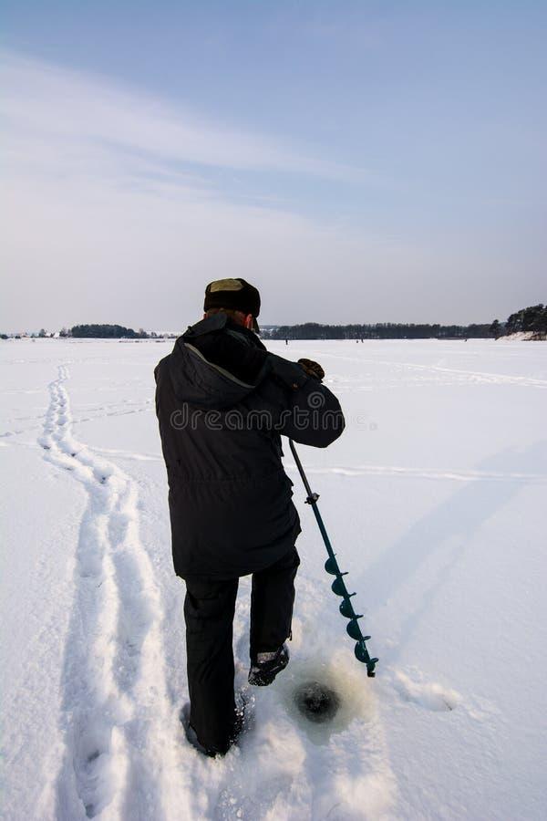 操练井为钓鱼老棕色钻子冰的冬天 图库摄影