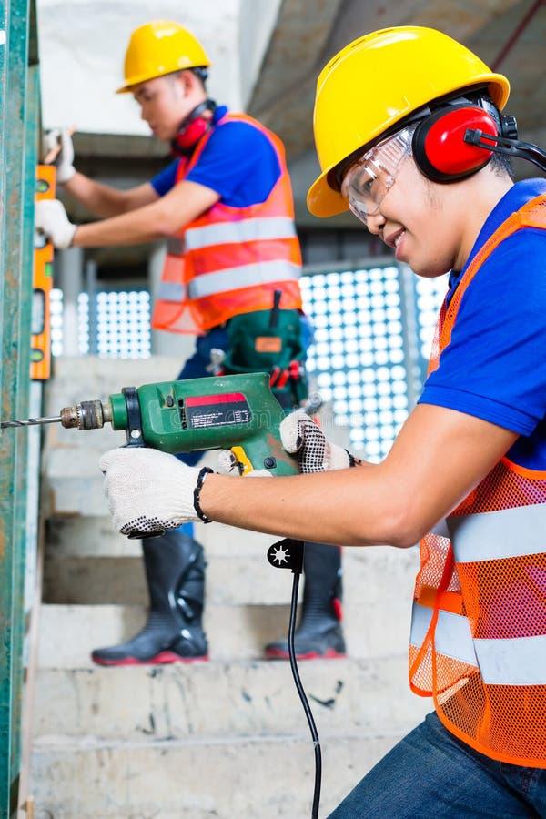操练在大厦墙壁的亚裔建筑工人 免版税库存照片