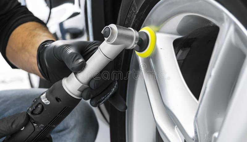 擦亮轮子的汽车波兰蜡工作者手 抛光的和擦亮的汽车盘 汽车详述 人在手和p上拿着一台磨光器 免版税库存照片