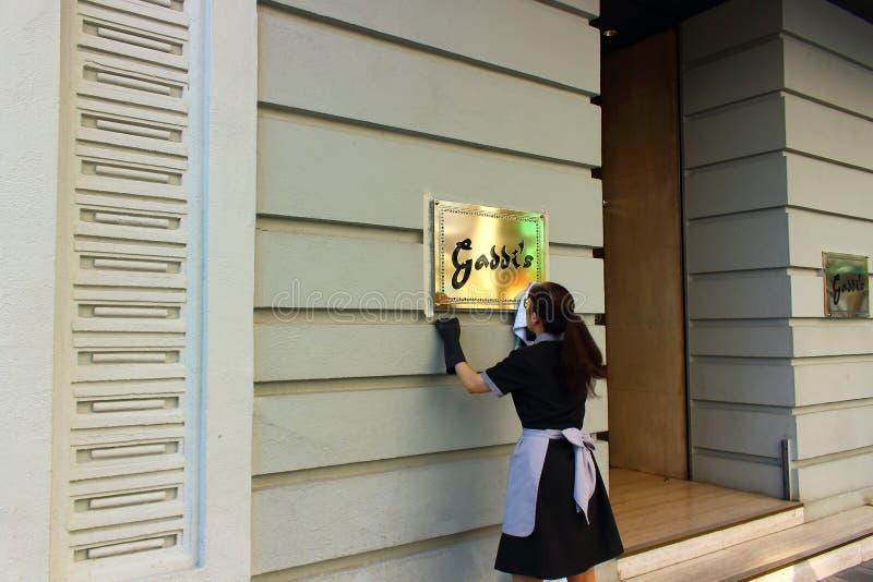 擦亮餐馆标志的妇女 图库摄影