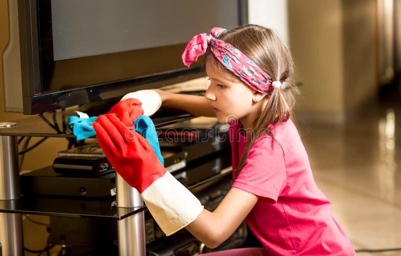 擦亮玻璃桌的橡胶手套的小女孩在生存roo 免版税图库摄影