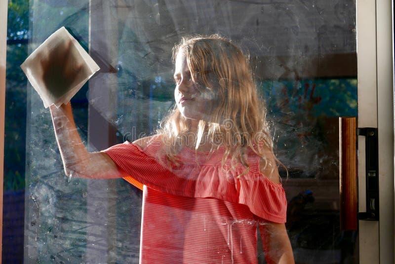 擦脏玻璃窗的女孩 图库摄影