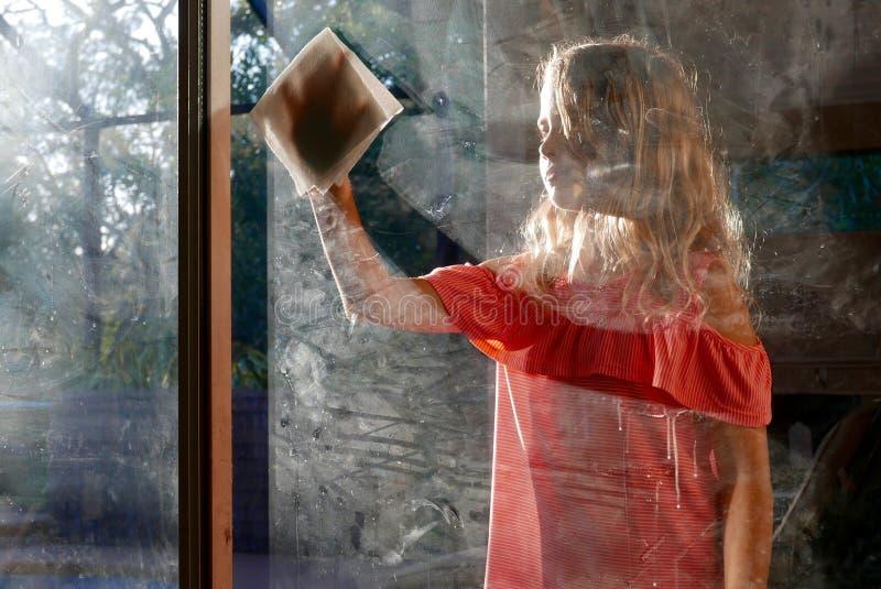 擦脏玻璃窗的女孩 免版税库存图片