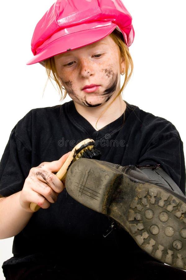 擦鞋童女孩小的光亮的鞋子 免版税库存图片