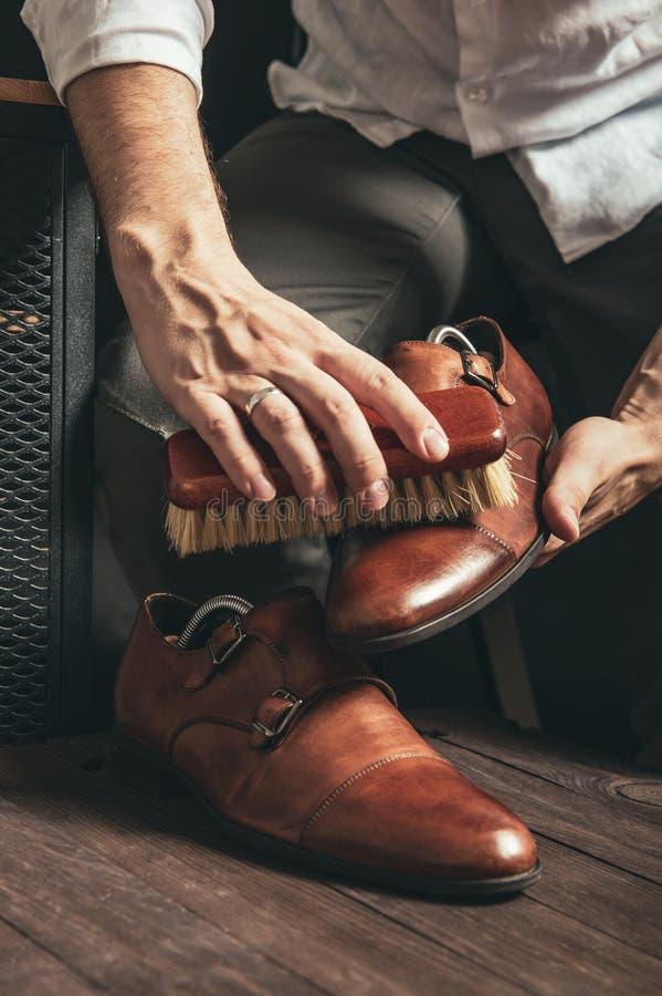 擦鞋童清洗棕色修士鞋子 免版税库存照片
