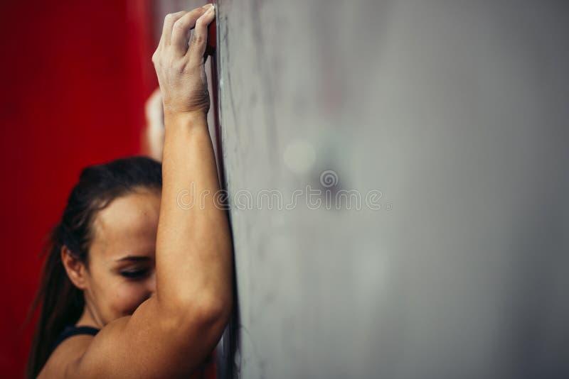 攀岩墙壁的适合的妇女在健身房 免版税库存图片