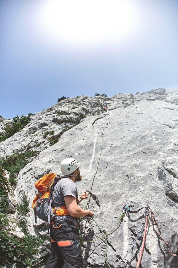 攀岩运动员在岩石的一个壁架站立并且系住伙伴 免版税图库摄影