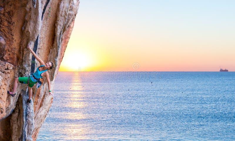 年轻攀岩运动员日出和海洋的明亮的图象背景的 库存照片
