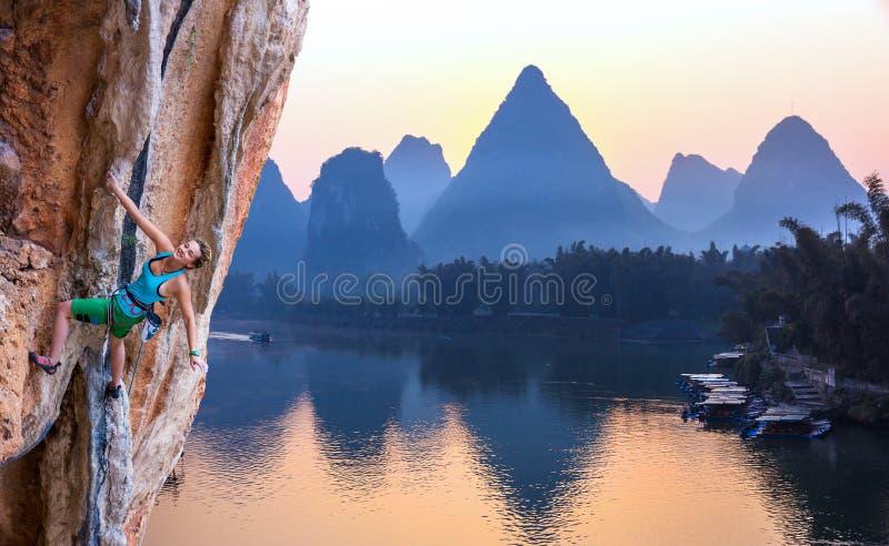 年轻攀岩运动员日出石灰岩地区常见的地形山的明亮的图象在中国和河 免版税库存照片