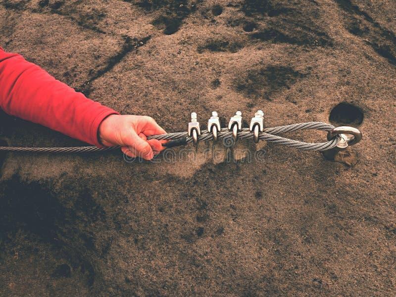 攀岩运动员钢被扭转的绳索的手举行在岩石停住的钢闩眼睛 库存照片
