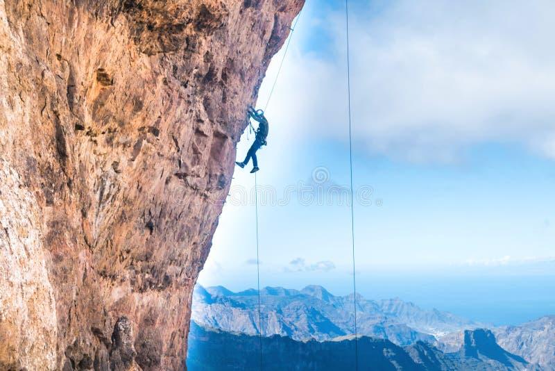 攀登伸出的峭壁的攀岩运动员 免版税库存图片