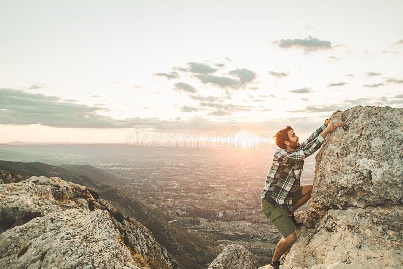 攀登在山的登山人一个岩石在日落 攀登岩石的远足者 库存照片