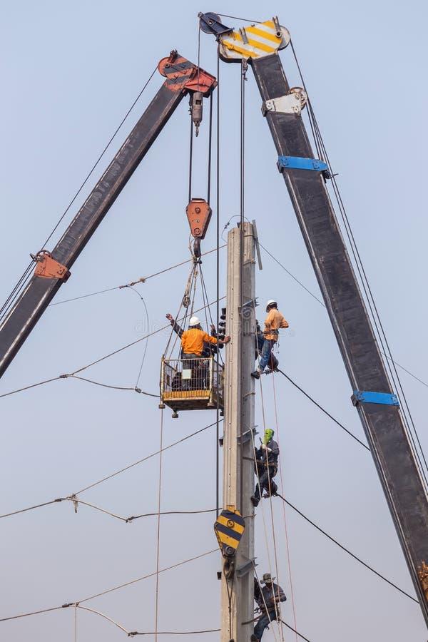 攀登在高度的电工工作在与大起重机和篮子的具体电力杆 免版税库存图片