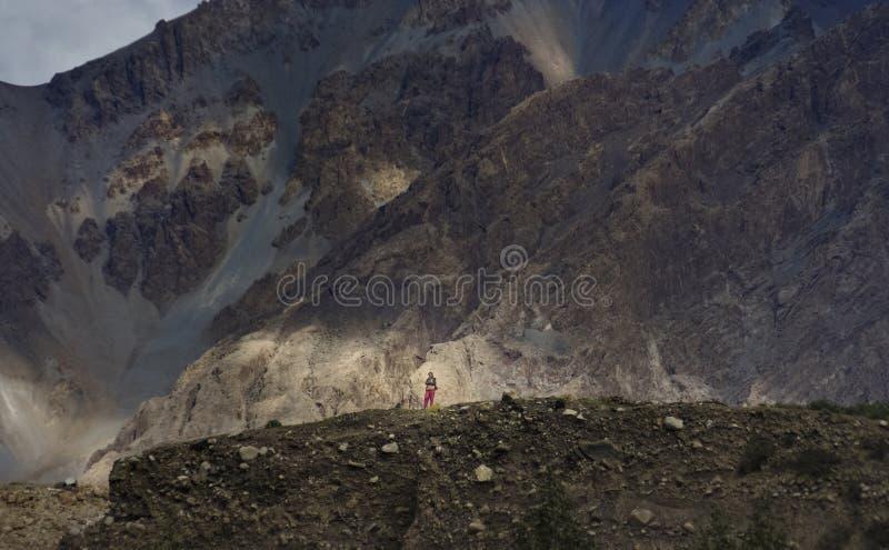 攀登山的女孩在村庄附近注意人的回归从山的 免版税库存照片
