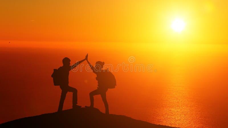 攀登山的男性和女性远足者 免版税库存图片