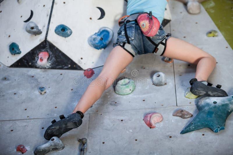 攀登岩石墙壁的青少年的女孩室内 库存照片