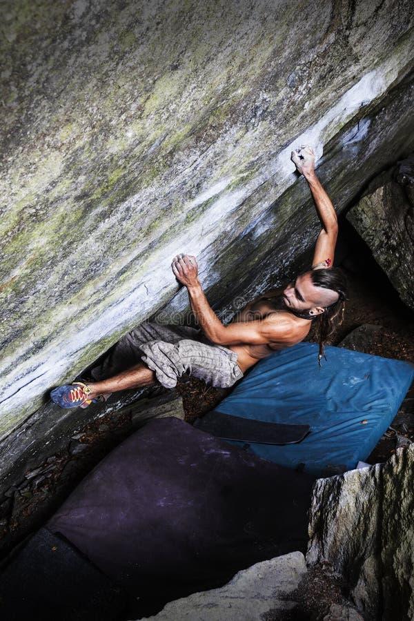 攀登石头的坚强的男孩 免版税库存图片