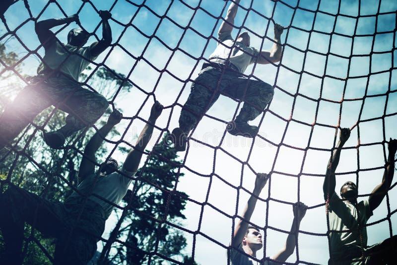 攀登绳索的军事战士在障碍桩期间 库存照片