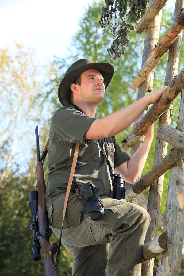 攀登与听力保护一个高位子的猎人 图库摄影
