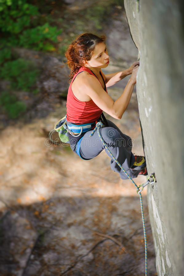 攀登与绳索的美丽的妇女登山人陡峭的岩石 免版税库存图片