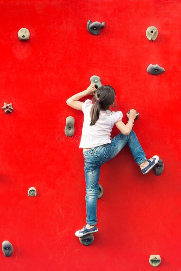 攀登墙壁的女孩在操场 库存图片