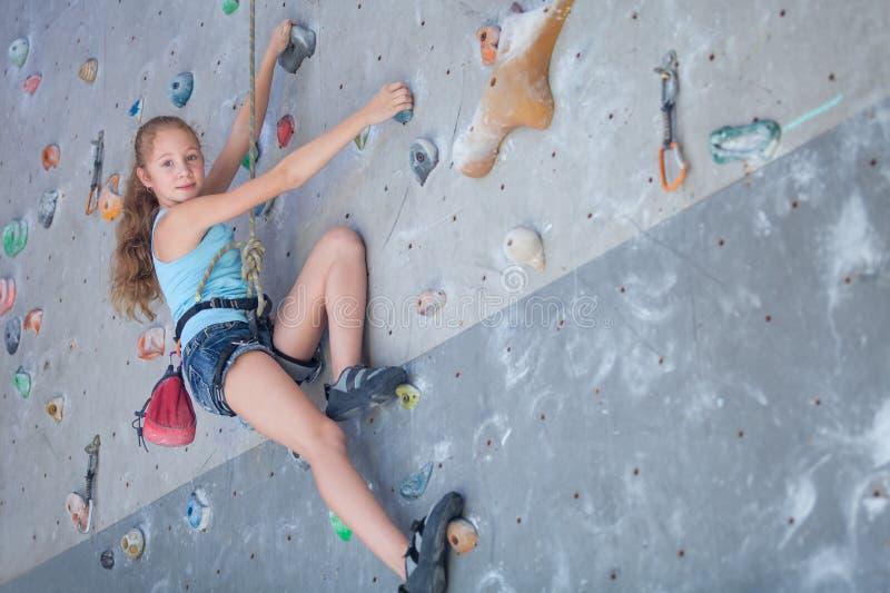攀登岩石墙壁的少年 免版税库存图片