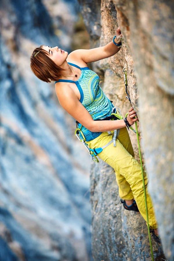 攀登峭壁的攀岩运动员 库存图片