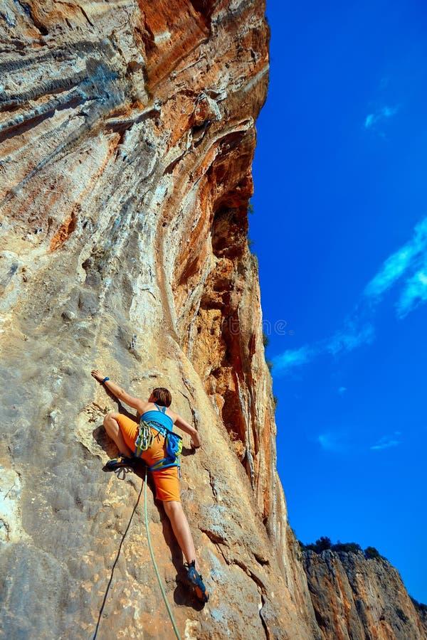 攀登峭壁的攀岩运动员 免版税库存图片