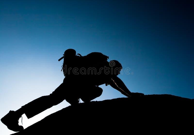 攀登年轻成人剪影在山顶顶部 免版税库存图片
