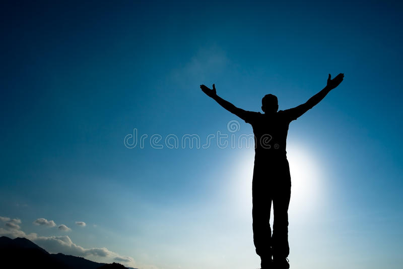攀登年轻成人剪影在山顶顶部 图库摄影