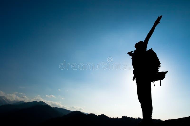 攀登年轻成人剪影在山顶顶部 免版税图库摄影