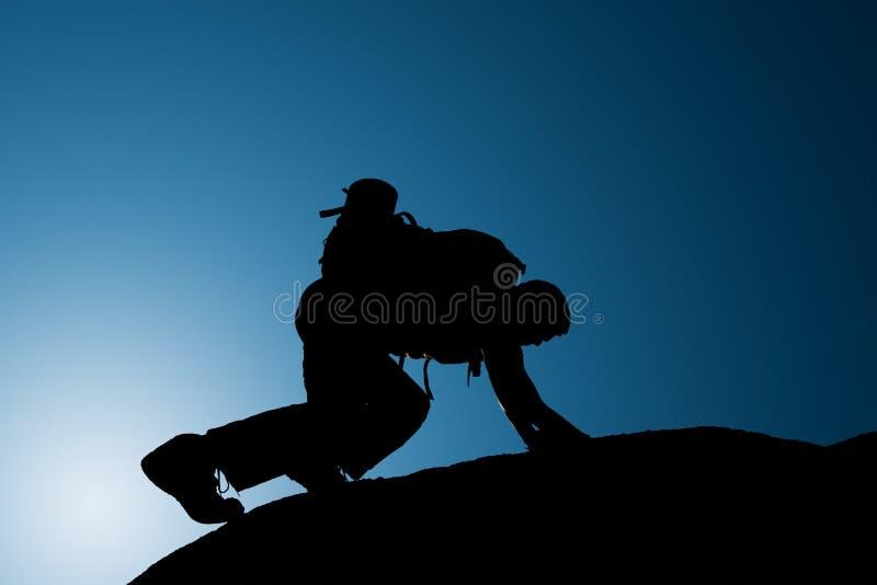 攀登年轻成人剪影在山顶顶部 免版税库存照片