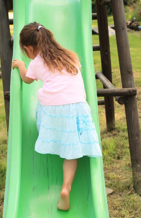 攀登幻灯片的小女孩 免版税库存图片