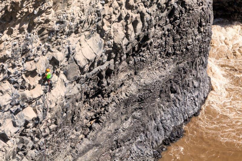 攀登自然岩石墙壁的年轻人 库存照片