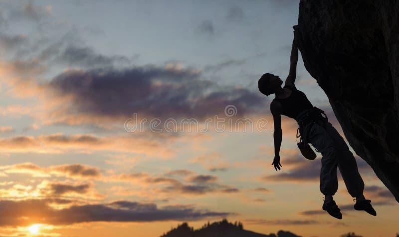 攀登陡峭的岩石墙壁的运动妇女剪影 库存照片